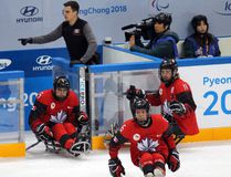 Shown here is James Sawchuk, athletic therapist for the Canadian Para ice hockey team, with the players before they hit the ice during the Paralympics in South Korea. (Photo by Shannon Morrison)