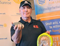 Gary Smith, owner of Red Devil Suba Supplies in Chatham, holds up a rock with iron ore he found on his diving adventures and a scuba mask following a presentation to the Rotary Club of Chatham Sunrise at Smitty's Restaurant on Tuesday. (TOM MORRISON, Postmedia Network)