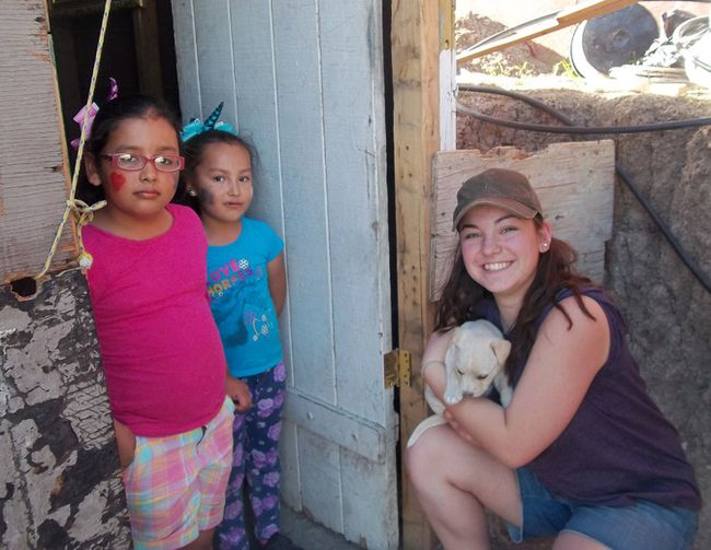 PHOTO COURTESY OF PALLISER REGIONAL SCHOOLS. Brant Christian School student Grace Meyer with two of the children, and their puppy, who were having a new home built for them.