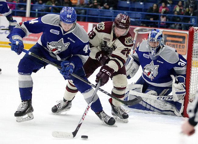 Cole Candella of the Sudbury Wolves  battles for the puck with Logan Denoble of the Peterborough Petes in front of Wolves goalie Marshall Frappier during OHL action in Sudbury, Ont. on Sunday, March 11, 2018. Gino Donato/Sudbury Star/Postmedia Network