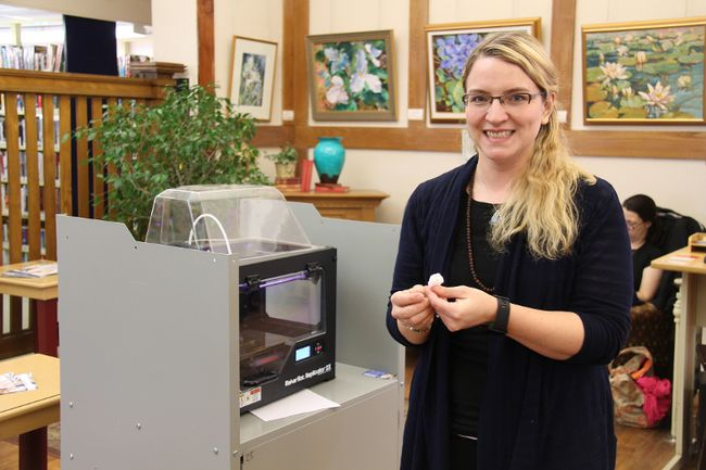 Pembroke Library assistant Kimberly Mayfield holds up a 3D-printed LEGO ring constructed with the library's Makerbot Replicator 2X Experimental Printer.