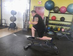 Farr Ramsahoye/Visionary Fitness Jan Murphy performs a Bulgarian split squat during his training with Visionary Fitness owner Farr Ramsahoye at 247 Fitness in Kingston this week.