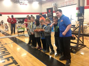 Kingston Scouts hold the first-place trophy for their winning bridge design, which was tested under pressure to see how much load it could bear at the Bridge the Engineering Gap event at St. Lawrence College in Kingston on Saturday.