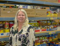 Executive Director Lori McRitchie poses with some of the stockpiled canned goods at the Airdrie Food Bank on Thursday, March 29. In 2018, the food bank has hit record-breaking numbers of families coming in for assistance.