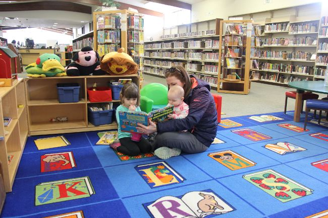 Sara Hendrikx reads a book to her daughters Meredith, left, and Malayna at the Strathroy Public Library. Fines for overdue kids and juvenile materials will be eliminated starting May 1 as part of a Middlesex County Library pilot project. JONATHAN JUHA/STRATHROY AGE DISPATCH/POSTMEDIA NETWORK