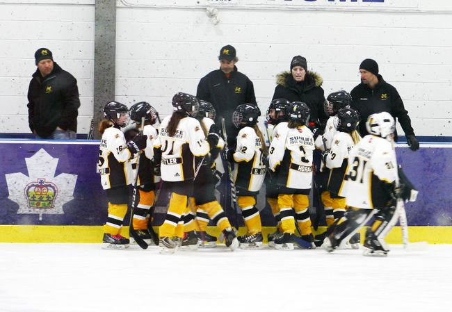 Members of the Mitchell Atom B girls receive a pep talk prior to a game this past weekend at the OWHA championships. SUBMITTED