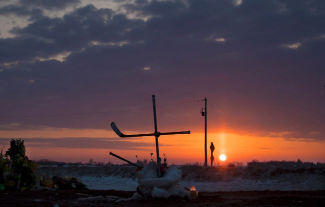 The sun rises across the Prairies on Tuesday morning as a cross made out of hockey sticks is seen at a makeshift memorial at the intersection where a fatal bus crash took place on Friday night near Tisdale, Sask. A bus carrying the Humboldt Broncos junior hockey team to a game in Nipawin collided with a tractor-trailer, killing 15 members of the organization and sending more than a dozen more to the hospital. THE CANADIAN PRESS/Jonathan Hayward