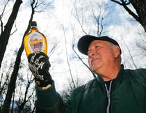 Luke Hendry/The Intelligencer  Maple syrup producer Ron Hubbs holds a bottle of syrup Tuesday in Hubbs' Sugarbush west of Rednersville. This year the operation has produced about a litre of syrup per each of its 250 tree taps, but producers farther north in central Hastings County are still frustrated by a cold spring that is preventing sap flow.