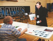 """Vulcan and Region Family and Community Support Services held a poverty simulation at the Cultural-Recreational Centre on Friday. Here, Lori Gair is forced to pawn a ring to make ends meet worth $100 to Bob Buckle, playing a role working at Big Dave's Pawn Shop. She receives $40 for the ring and is surprised, saying: """"It was my grandmother's ring."""" Jasmine O'Halloran Vulcan Advocate"""