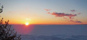 A returning spring sun sets over Lake Superior ice at Montreal River Harbour.