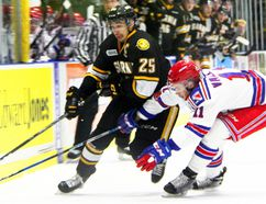 Sarnia Sting's Jordan Kyrou tries to move the puck by Kitchener Rangers defender Giovanni Vallati in Game 3 of the OHL Western Conference semifinal Tuesday at Progressive Auto Sales Arena in Sarnia. (Tyler Kula/Sarnia Observer)