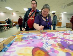 Jaimie Tremblay adds to the painted silk that was created collectively by attendees at Get Connected, a community mental health awareness event in Napanee on Friday. (Meghan Balogh/The Whig-Standard/Postmedia Network)