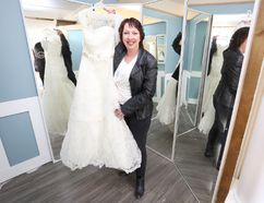 Michelle McCaugherty holds a donated wedding dress in Dawn House's new, soon-to-open bridal boutique. (Meghan Balogh/The Whig-Standard)