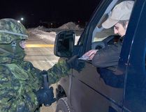 A Wing Auxiliary Security Force member checks a driver's identification during a previous exercise at 22 Wing / Canadian Forces Base North Bay. Photo by Cpl Joseph Morin
