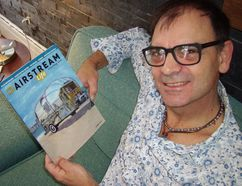 St. Thomas artist Michael Lambert and the spring number of Airstream Life, for which he painted the cover image. (Eric Bunnell/Times-Journal)