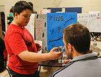Jake Perry, a Grade 7 student, offers one of the judges a smell of his Pine Pitch Salve, a product he developed for the KidPreneur Fair at J.J. O'Neill Catholic School in Napanee on Tuesday. (Julia McKay/The Whig-Standard)