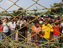 (FILES) In this file photo taken on March 18, 2018 minority Rohingya Muslims gather behind Myanmar's border lined with barbed wire fences in Maungdaw district, located in Rakhine State bounded by Bangladesh. Canada should take in Rohingya refugees and press other nations to do the same, Prime Minister Justin Trudeau's special envoy to Myanmar said April 3, 2018. Special envoy Bob Rae -- on the heels of his fact-finding mission to Bangladesh and Myanmar -- also urged Ottawa to increase humanitarian aid for the Rohingya, to continue to target human rights abusers with sanctions and to gather and protect evidence for possible future trials. Joe FreemanJOE FREEMAN/AFP/Getty Images