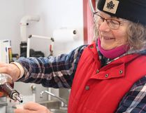 Lori Costello, a local maple syrup producer at Bella Hill Maple Farms, pours out a sample of syrup to her sugar bush guests. Supplied Photo
