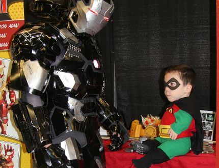 Five-year-old Robin Fortier, fittingly suited up as Batman's sidekick Robin, gets a close-up view of Brampton Ironman's suit Saturday in the Cosplay Corner of the Comicon Timmins event held at the McIntyre Curling Rink this weekend.