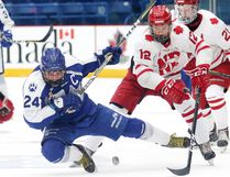 Mathieu Dokis-Dupuis of the Sudbury Nickel Capital Wolves gets tripped up by Cordel Larson of the Notre Dame Hounds during 2018 Telus Cup action in Sudbury, Ont. on Tuesday April 24, 2018. Gino Donato/Sudbury Star/Postmedia Network