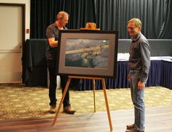 Henry Vos stands beside the Brian Hohner painting of the Canso that he commissioned for the Save the Canso group. Hohner is at left behind the painting. Prints of the painting will be sold as a fundraiser for the Canso.