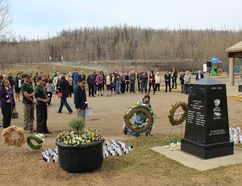 People lay flowers at a cenotaph at J. Howard Pew Park as part of the National Day of Mourning ceremony in Fort McMurray, Alta. on Saturday, April 28, 2018. Vincent McDermott/Fort McMurray Today/Postmedia Network