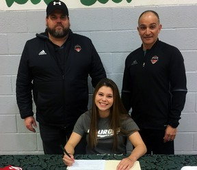 St. John's Olivia Pomponio signs her letter of intent to attend Lourdes University while head soccer coach (left) Jackie Donovona and Pomponio's father, Peter, look on.