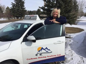 Debbie Sherwood poses with one of the fleet in the Cochrane Driving Academy before heading off to Saudi Arabia.
