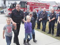 KEVIN RUSHWORTH HIGH RIVER TIMES/POSTMEDIA NETWORK. Len Zebedee, now former High River Fire Department (HRFD) fire chief, walks up his driveway with friends and family members present while local firefighters flank the drive on April 30. Members with the HRFD, Foothills Fire Department—including Cayley and Blackie halls—were on hand to surprise Zebedee, providing him his last ride home in Engine 42 alongside a parade of fire vehicles.