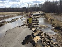 Woodlands County Mayor Jim Rennie stands on the remains of Flats Road, which suffered substaintial damage from the floods (Submitted | Jim Rennie).