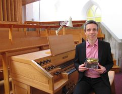 Jack Evans/For The Intelligencer Matthieu Lattreille holds a copy of his first CD, recently released, as he sits on the organ bench in St. Thomas Anglican Church.