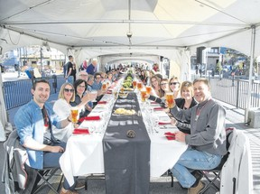 Diners toast at the start of the Canmore Uncorked Long Table dinner event under a tent in front of the Canmore Civic Centre plaza on Thursday, May 4, 2017. Pam Doyle/. pamdoylephoto.com