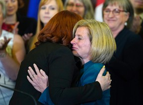 Carlynn McAneeley (left), a survivor of sexual violence, is hugged by Alberta Premier Rachel Notley (right) at the Alberta Legislature on May 1.  Larry Wong/Postmedia Network