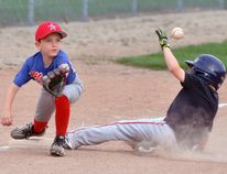 Stretching for the ball for a potential out at third base was Nate Uniac (left) of the Mitchell Rookie (Brown) baseball team last Wednesday, May 9 during exhibition action against visiting London. The higher-ranked visitors defeated the Astros, 22-6. ANDY BADER/MITCHELL ADVOCATE