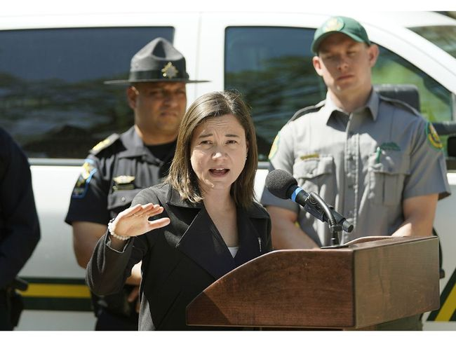 Shannon Phillips (Alberta Environment and Parks Minister, at podium) announced enforcement on public land and parks over the May long weekend and throughout the summer. In background are Kanwarjit Ghumman (left, Traffic Sheriff) and Austin Toly (right, Conservation Officer). Larry Wong/Postmedia Network