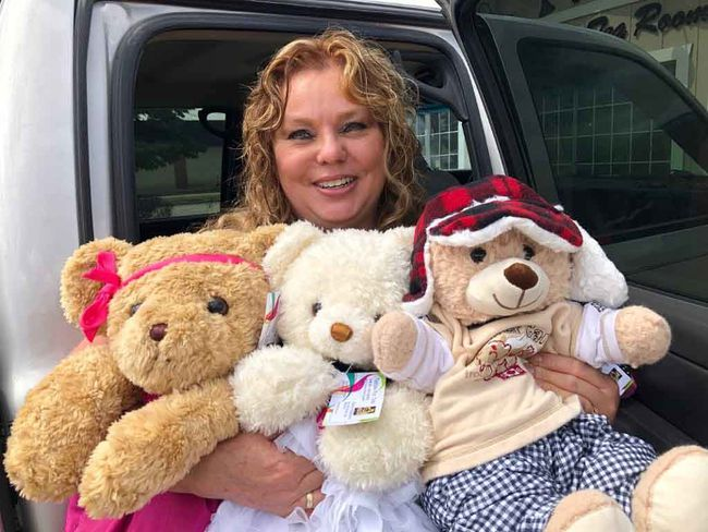 Teddies for Tots founder Sharon Hildebrand with three teddy bears all cleaned, dressed and ready for hugs.