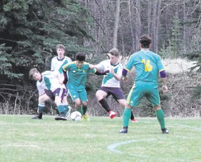 Canmore Collegiate's Kota Postma eludes a pair of Holy Trinity Academy defenders during a senior boys high school soccer game on May 9 at Millennium Park. The Canmore Crusaders tied the Okotoks-based Knights 2-2 in the Foothills High School Soccer League contest.