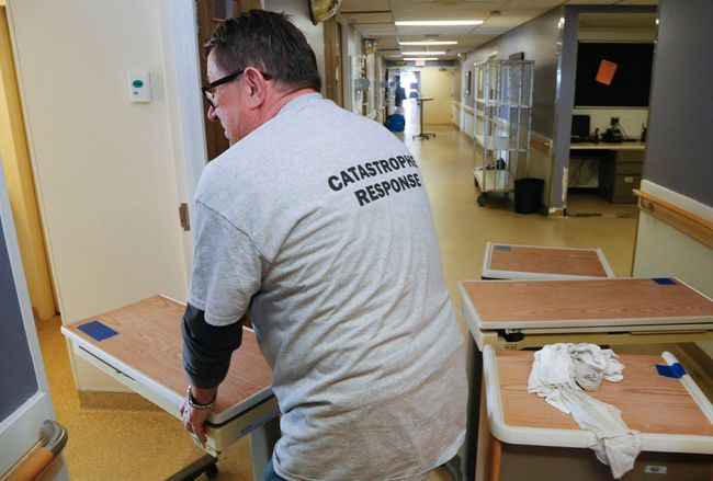 Luke Hendry/The Intelligencer Steve Kowalczyk of FirstOnSite Restoration Ltd. returns a patient table to a room on the Quinte 5 floor of Belleville General Hospital Friday, May 11 in Belleville. The floor was damaged in a May 8 fire and is expected to be out of service until the week of July 9.