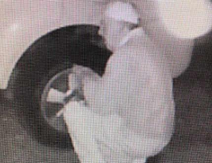 Gananoque police have released this image of a man kneeling by the tire of an SUV in a mischief case. (Submitted photo)