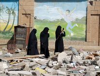 Yemeni women take pictures of the damage following an air-strike carried out by the Saudi-led coalition on a school and a bowling club, in the capital Sanaa, on February 12, 2016. / AFP / MOHAMMED HUWAISMOHAMMED HUWAIS/AFP/Getty Images