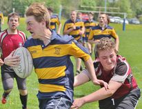 St. Michael's Hunter Sawitzky tries to outrun the tackle of Northwestern's Jayden Schweitzer during the Huron-Perth junior boys rugby game Friday at St. Mike's. (Cory Smith/The Beacon Herald)