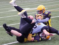 The North Bay Bulldogs bantam and junior varsity teams lost their 2018 Ontario Provincial Football League season-openers at the Steve Omischl Sports Fields Complex, Saturday, as the visiting Clarington Knights won 26-12 and 24-0, respectively. In the photo above, junior varsity Bulldogs Christian Huter (29) and Miguel Allard (99) team up to take down a Knights ball carrier. Dave Dale / The Nugget