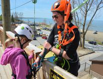 Ascent Aerial Park employee Jessica Baker prepares Lily Erner, 10, for a jump at the Ascent Aerial Park at Sauble Beach on Monday. (Rob Gowan The Sun Times)