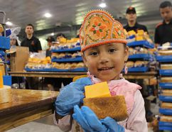 Four-year-old Madisyn Hess, Miss Six Nation's Tiny Tot, helps hand out bread and cheese on Monday at the Gaylord Powless Arena. Michelle Ruby/The Expositor