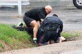 Andy Gagne, a principal with the Near North District School Board, helps North Bay Police Const. Richard Hampel take down and handcuff a suspect near the Algonquin and Greenwood avenue intersection Saturday afternoon. Dave Dale / The Nugget