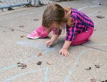 A child colours in her chalk outline in front of a daycare.