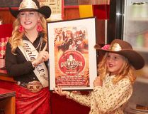KASSIDY CHRISTENSEN HIGH RIVER TIMES/POSTMEDIA NETWORK. Kira Schneider, Miss Alberta High School Rodeo Queen, left, and Willow Kingsmith, Little Britches Rodeo Princess, right, presented the Guy Weadick Days 2018 poster.