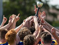 Members of the BCI senior boys rugby team reach to touch the trophy after defeating St. John's College to claim the Brant County high schools senior boys rugby championship on Thursday in Brantford. (Brian Thompson/The Expositor)