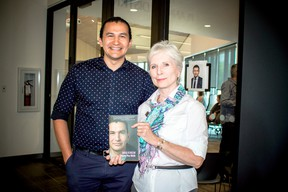 Berry displays Kinew's book as they stand together outside the theatre at Gaynor Family Library on May 25.