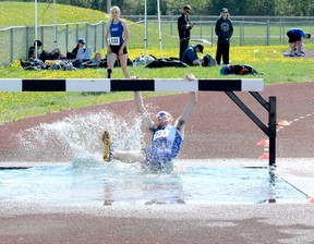 Connor Stewart, of Timmins High & Vocational School, reaches up in an attempt to grab onto the jump as he slides into the water hazard during the opening lap of the Open Boys 2,000-metre steeplechase event at the 2018 NEOAA Track & Field Championships at Timmins Regional Athletics and Soccer Complex on Wednesday. Stewart managed to overcome the setback and finished in third place.  THOMAS PERRY/THE DAILY PRESS
